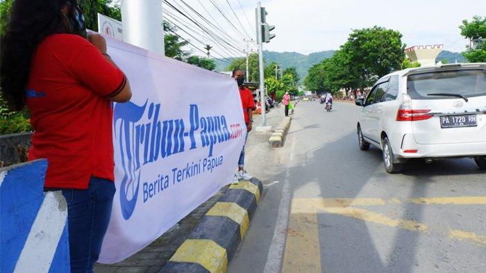 Sales Promotion Girl (SPG) sedang membentangkan baliho Tribun-Papua.com di Lampu Merah Brimob Kotaraja, Kota Jayapura, Provinsi Papua, Jumat (18/6/2021).