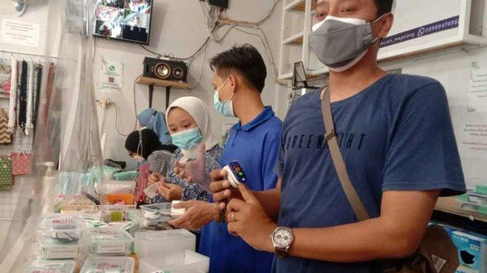 Johanes Aditya Sanjaya (38) dan Theresia Sulistiowati (36), warga Mertoyudan, Kabupaten Magelang, Jawa Tengah, meminjamkan puluhan oximeter bagi warga yang sedang menjalani isolasi mandiri (isoman), Selasa (27/7/2021).
