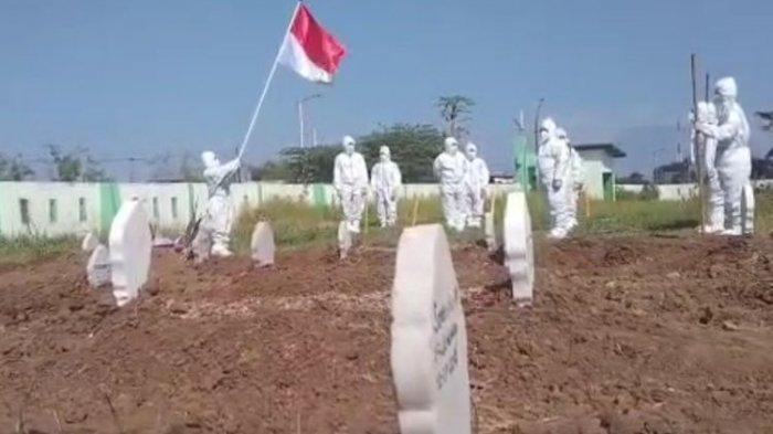 UPACARA BENDERA—Relawan tim pemakaman jenazah pasien covid-19 menggelar upacara bendera untuk memperingati HUT RI Ke-76 di halaman tempat pemakaman umum Pagu Indah, Kelurahan Manisrejo, Kecamatan Taman, Kota Madiun, Jawa Timur, Minggu (15/8/2021).