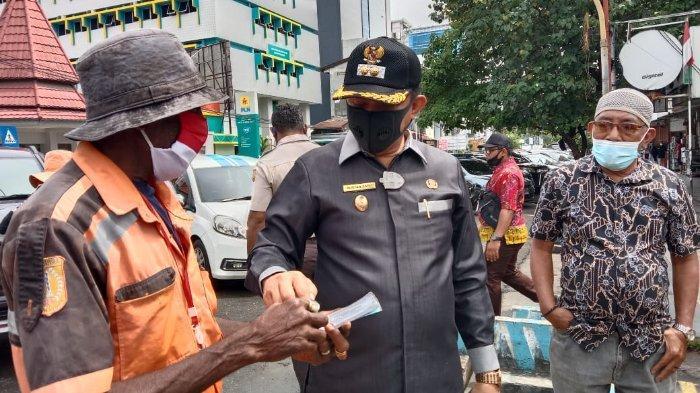Wakil Wali Kota Jayapura, Rustan Saru (tengah) bersama seorang tukang parkir di Jayapura