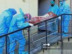 anggota-staf-medis-yang-mengenakan-apd-membawa-jenazah-pasien-covid-19.jpg