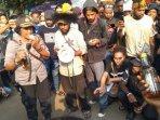 mahasiswa-asal-papua-saat-menyerahkan-kiriman-minuman-keras-dari-oknum-polisi.jpg