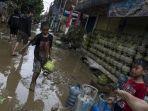 sejumlah-warga-melintas-di-area-pemukiman-yang-sempat-terendam-banjir.jpg