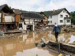 seorang-pria-berjalan-melewati-banjir-menuju-rumah-rumah-yang-hancur.jpg