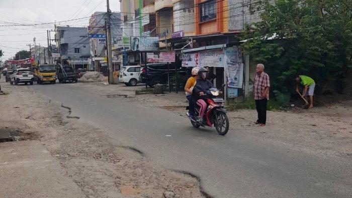 Kondisi Jalan Pemuda Kelurahan Tampan, Kecamatan Payung Sekaki, Pekanbaru, yang rusak parah. Nampak warga mendorong mobilnya akibat masuk lubang. Foto diambil Jumat (11/12/2020).