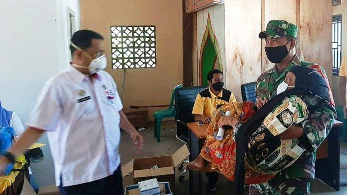Seorang Babinsa tengah menggendong seorang nenek menuju lokasi vaksinasi di Puskesmas Pagaran Tapah Darussalam.