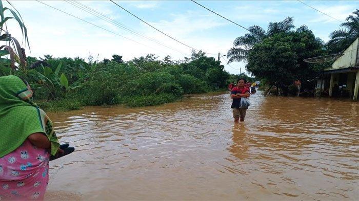 Wanita berjalan di tengah genangan banjir di Desa Suka Ramai Kec Tapung Hulu, Kampar, Riau, Sabtu (25/9/2021)