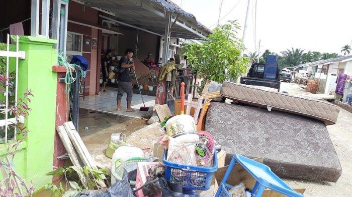 Penghuni Perumahan Pesona Harapan Indah, Jalan Cengkeh, Kota Pekanbaru tampak bersih-bersih, Minggu (25/4/2021) pasca banjir melanda selama hampir empat hari.