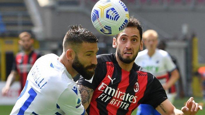 Bek Sampdoria Lorenzo Tonelli (kiri) dan gelandang AC Milan Hakan Calhanoglu mengejar bola selama pertandingan sepak bola Serie A Italia AC Milan vs Sampdoria pada 3 April 2021 di stadion San Siro di Milan.