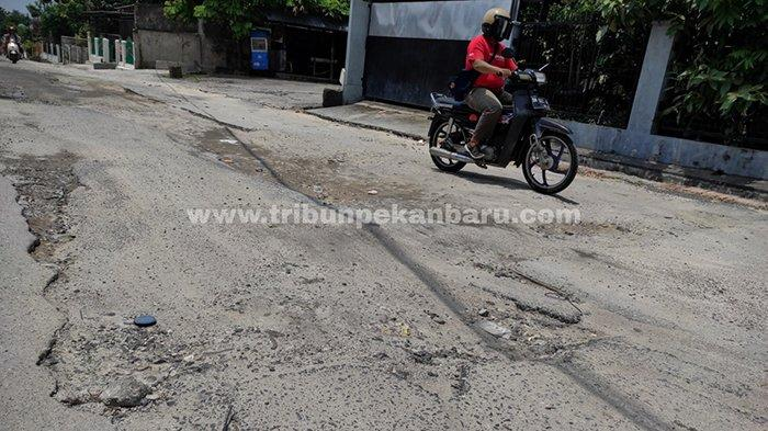 Kendaraan melintas di bekas galian perpipaan limbah rumah tangga di Jalan Melati, Kecamatan Sukajadi, Pekanbaru yang rusak, Selasa (13/4/2021).