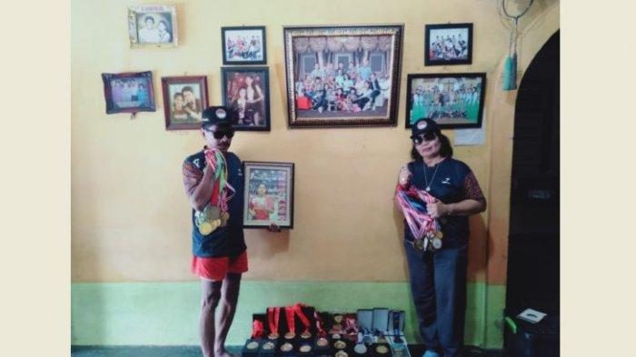 Ayah dan ibu foto bersama foto Ratri dan koleksi medali Ratri di rumahnya di Desa Siabu Kecamatan Salo, Senin (5/9/2021).