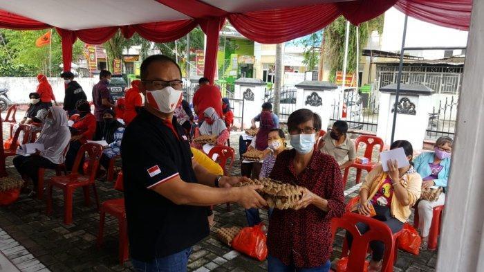 Anggota DPRD Pekanbaru Robin Eduar SH MH (kiri) menyerahkan bantuan sembako kepada warga, saat acara Sosialisasi Perda akhir pekan lalu di Jalan Pemuda Gg Mesjid Kecamatan Payung Sekaki.