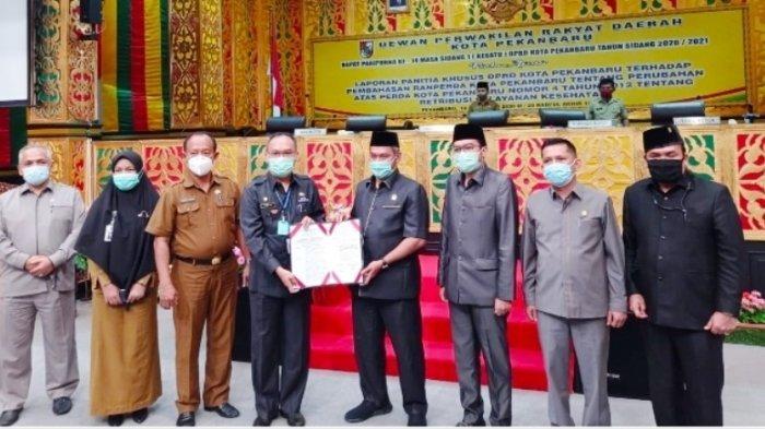 Ketua Pansus Retribusi Pelayanan Kesehatan Ruslan Tarigan SPd (kanan) foto bersama pimpinan DPRD Pekanbaru, Asisten I Azwan, usai mengesahkan Ranperda Retribusi Pelayanan Kesehatan menjadi Perda Kota Pekanbaru, Senin kemarin.