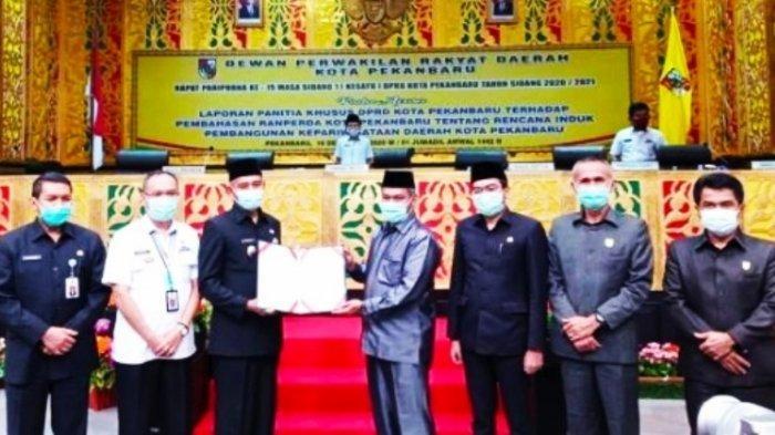 Ketua DPRD Pekanbaru Hamdani SIP (kanan) menyerahkan draf Perda Rippda Pekanbaru kepada Wakil Walikota Pekanbaru Ayat Cahyadi di dampingi Wakil Ketua DPRD Ir Nofrizal MM, saat Rapat Paripurna awal pekan kemarin.