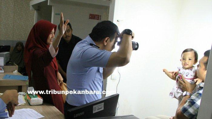 Petugas sedang berusaha memotret seorang anak yang akan membuat paspor di Kantor Imigrasi Kelas I Pekanbaru, Senin (21/1/2019). (Tribun Pekanbaru/Doddy Vladimir)