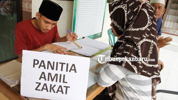 Amil Zakat menerima pembayaran zakat fitrah dari warga wajib zakat di Masjid Raya Al Khairat Jalan Durian, Pekanbaru, Selasa (19/5/2020). (www.tribunpekanbaru.com/Doddy Vladimir)