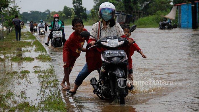 FOTO: Sejumlah Anak-Anak di Pekanbaru Dorong Motor yang Mogok Akibat Banjir - foto_sejumlah_anak-anak_di_pekanbaru_dorong_motor_yang_mogok_akibat_banjir_1.jpg