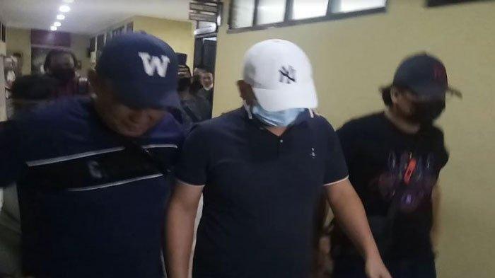 Galak Saat Aniaya Perawat Wanita Setelah Ditangkap Polisi, Pria Penganiaya Perawat Tundukan Kepala. Foto: Tersangka digiring polisi