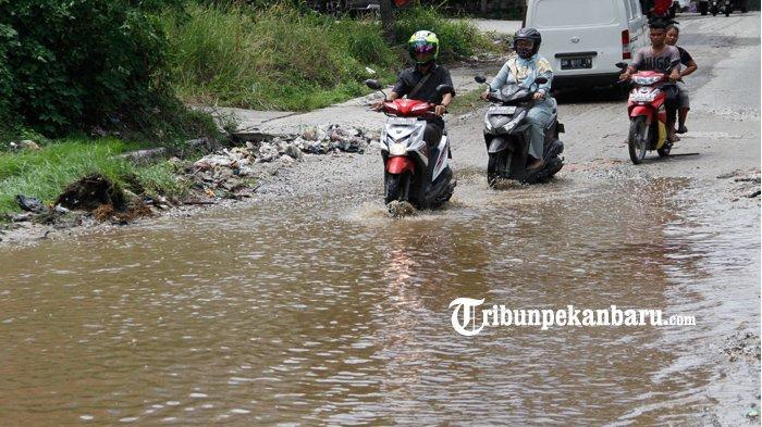 Sejumlah kendaraan saat melintas di Jalan Pemuda, Kecamatan Payung Sekaki, Pekanbaru yang rusak parah dan tergenang air, Selasa (18/8). Warga meminta kepada pemerintah terkait agar segera memperbaiki jalan yang rusak parah  tersebut karena kondisi jalan rusak sudah berlangsung lama.