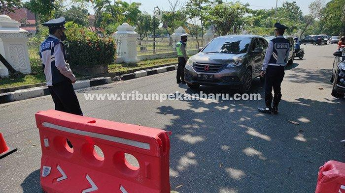 Personel kepolisian dan Dishub saat melakukan penyekatan dalam pelaksanaan Pemberlakuan Pembatasan Kegiatan Masyarakat (PPKM) level 4 di Jalan Thamrin, Pekanbaru, Selasa (27/7/2021).