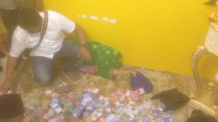 Petugas sedang menghitung uang dalam penggerebekan sebuah rumah di Kampung Dalam