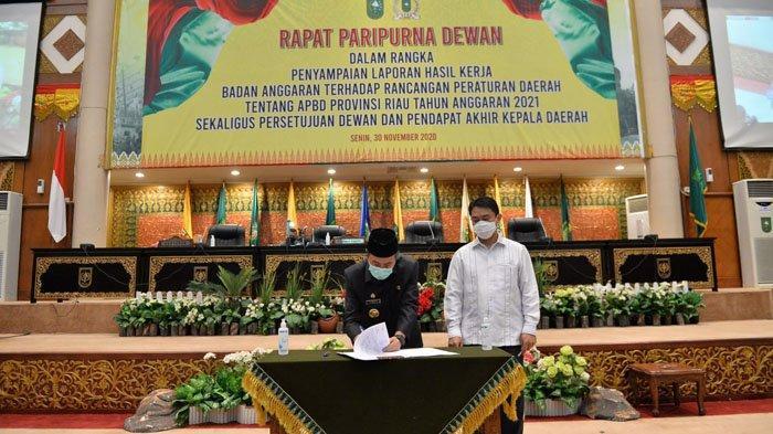 Gubernur Riau Syamsuar dan Wakil Ketua DPRD Riau, Hardianto, menandatangani Pengesahan APBD Riai 2021 dilakukan secara resmi dalam rapat paripurna di Gedung DPRD, Senin (30/11/2020).
