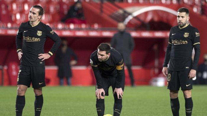 Penyerang Barcelona asal Argentina Lionel Messi (tengah) menunggu untuk menendang bola antara gelandang Prancis Barcelona Antoine Griezmann (kiri) dan bek Spanyol Barcelona Jordi Alba selama pertandingan sepak bola Liga Spanyol antara Granada dan Barcelona di stadion Los Carmenes di Granada pada 9 Januari 2021.