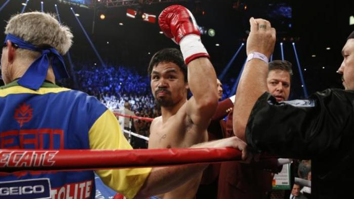 Manny Pacquiao mengangkat tangannya