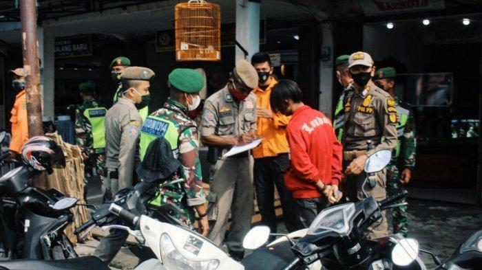 Petugas mendata pelanggar prokes pada operasi perdana pengetatan penegakan disiplin prokes di Jalan Jenderal Sudirman Tembilahan, Kabupaten Inhil, Selasa (4/5/2021).