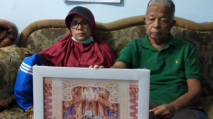 Kedua orangtua Putri Wahyuni, memegang foto pernikahan korban bersama suaminya saat disambangi di kediaman, Senin (11/1/2021).