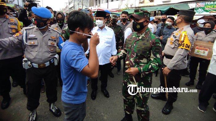Pangdam I Bukit Barisan Mayjen TNI Hasanuddin membagikan masker di Pasar Kodim, Pekanbaru, Rabu (10/2/2021).