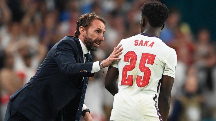 Pelatih Inggris Gareth Southgate (kiri) berbicara dengan gelandang Inggris Bukayo Saka selama pertandingan sepak bola final UEFA EURO 2020 antara Italia dan Inggris di Stadion Wembley di London pada 11 Juli 2021.