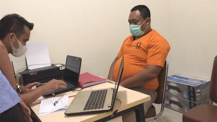 Tersangka berinisial N (baju oren) pelaku pemalsuan surat bebas Covid-19, sedang diperiksa penyidik. Pelaku sehari-hari berprofesi sebagai calo tiket bandara Sultan Syarif Kasim II, Pekanbaru.