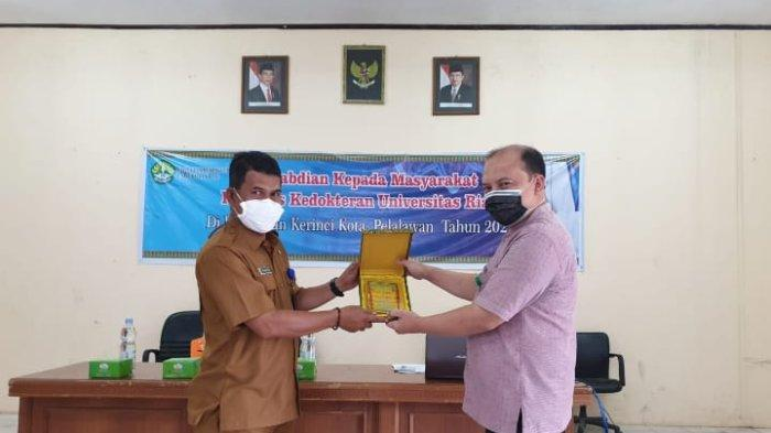 Pemberian kenang-kenangan kepada pihak Kelurahan pada kegiatan pengabdian dosen KJFD Farmakologi Fakultas Kedokteran Universitas Riau