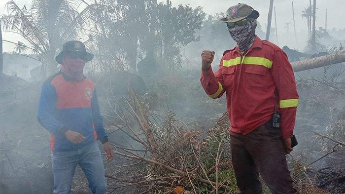 Petugas melakukan pendinginan di lokasi karhutla yang merupakan lahan gambut di Kuala Kampar Pelalawan.