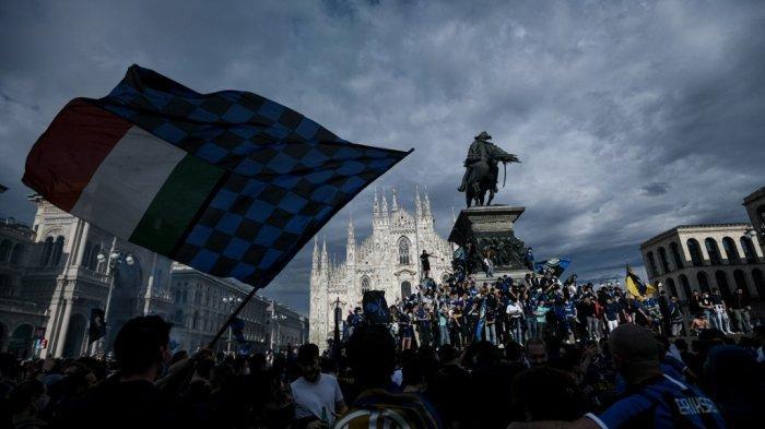 Pendukung Inter Milan mengibarkan bendera saat mereka merayakan scudetto di Piazza Duomo di Milan pada 2 Mei 2021, setelah tim mereka memenangkan gelar Kejuaraan Serie A Italia. Inter Milan merebut gelar Serie A sepak bola untuk pertama kalinya sejak 2010 pada 2 Mei 2021 ketika rival terdekatnya Atalanta bermain imbang 1-1 di Sassuolo.