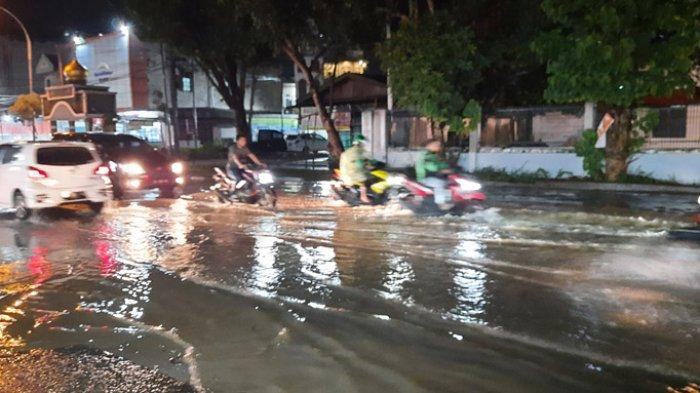 Pengendara melintas di satu genangan banjir di ruas Jalan Ahmad Yani, Kota Pekanbaru.