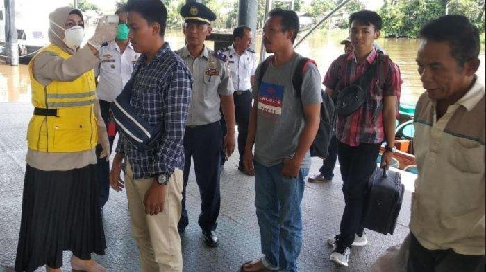 Tangkal Virus Corona, Petugas Periksa Suhu Tubuh Penumpang yang Datang di Pelabuhan Sungai Duku