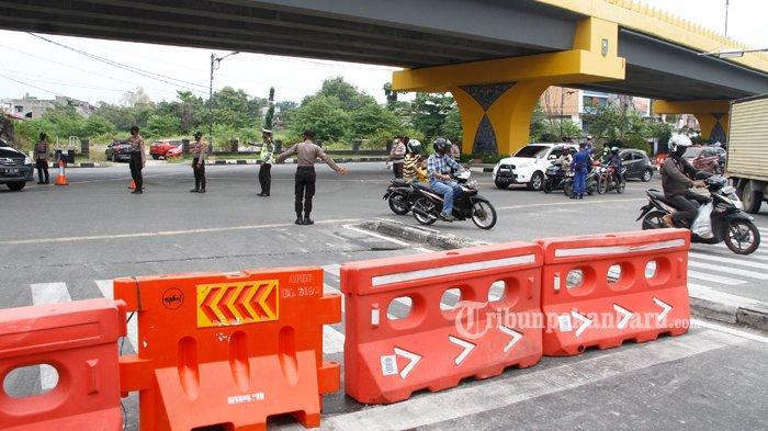 Sejumlah petugas saat mengatur arus lalu lintas di lokasi penyekatan Jalan Jenderal Sudirman, Pekanbaru, Sabtu (31/7/2021). Penyekatan dilakukan guna mengurangi mobilitas masyarakat sesuai Surat Edaran Walikota Pekanbaru Nomor 16/SE/SATGAS/2021 tentang pedoman dasar pelaksanaan PPKM Level 4 Kota Pekanbaru.