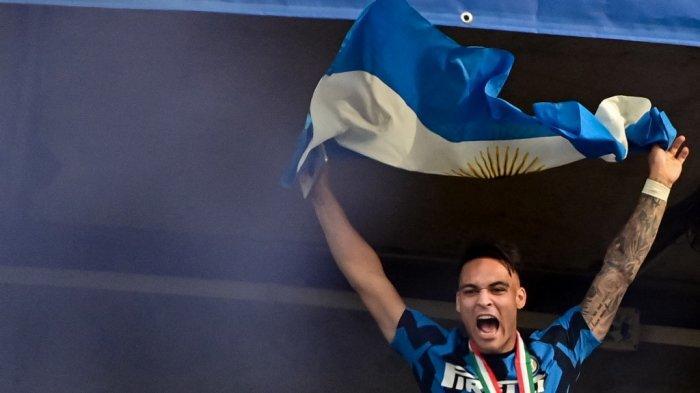 Penyerang Inter Milan asal Argentina Lautaro Martinez mengibarkan bendera Argentina saat para pemain Inter Milan merayakan kemenangan Serie A kejuaraan Scudetto 2020-2021, dari salah satu menara stadion menghadap penggemar yang berkumpul, setelah pertandingan sepak bola terakhir Serie A Italia Inter Milan vs Udinese pada 23 Mei, 2021 di stadion San Siro di Milan.