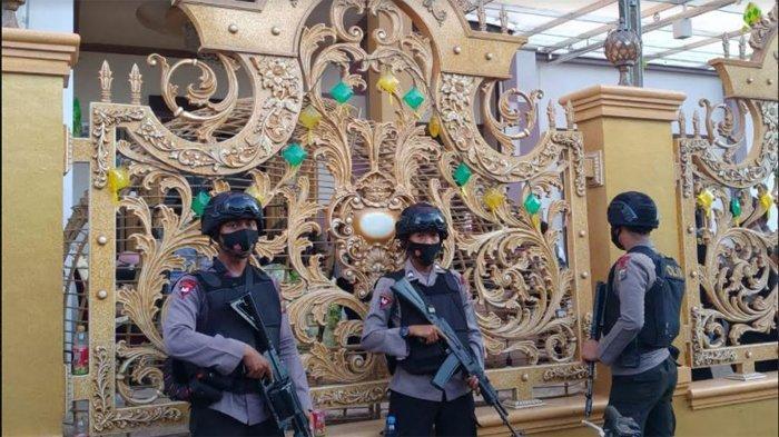 Personel Brimob bersenjata lengkap tampak berjaga-jaga di depan rumah mewah di Kampung Dalam, Pekanbaru. Rumah ini digeledah polisi, Rabu (16/6/2021)/Rizky Armanda