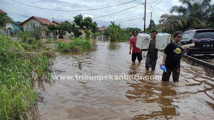 Warga Perumahan Fauzan Asri di Jalan Kesadaran, Gg Wicaksana, Kelurahan Tangkerang Labuai, Kecamatan Bukit Raya, Kota Pekanbaru ngungsi di tengah banjir, Senin (29/3/2021).