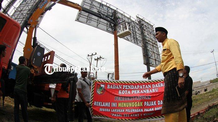 FOTO: Tidak Bayar Pajak, Bapenda Pekanbaru Segel Baliho - petugas-bapenda-pekanbaru-menyegel-tiang-baliho-simpang-jalan-tuanku-tambusai-1.jpg