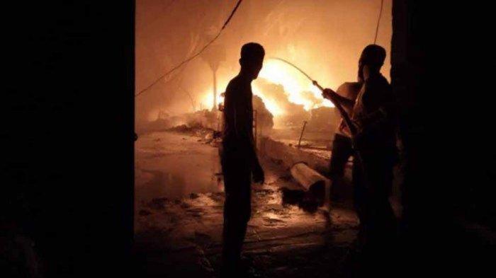 Petugas berjibaku memadamkan api di PT Lexim Global Indo di Jalan Raya Semambung, Desa Driyorejo, Kecamatan Driyorejo, Minggu (16/5/2021).