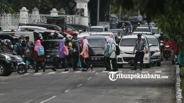 FOTO: Petugas Dishub Pekanbaru Atur Lalu Lintas Bantu Seberangkan Anak Sekolah - petugas-dishub-seberangkan-murid-sekolah-di-jalan-sultan-syarif-kasim_20181102_151940.jpg