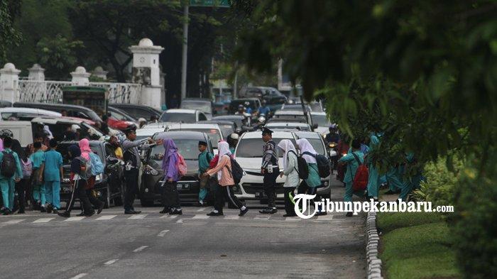 FOTO: Petugas Dishub Pekanbaru Atur Lalu Lintas Bantu Seberangkan Anak Sekolah - petugas-dishub-seberangkan-murid-sekolah_20181102_151947.jpg
