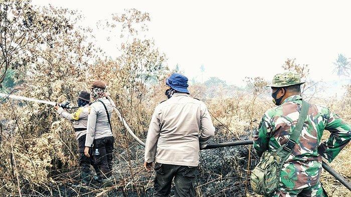 Petugas gabungan setempat bersama masyarakat melakukan pendinginan di lokasi Karhutla di Kecamatan Gaung, Kabupaten Inhil, Riau.