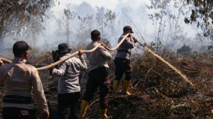 Petugas kepolisian memadamkan titik api karhutla di Kecamatan Bunga Raya, Kabupaten Siak, Riau, Senin (8/3/2021).