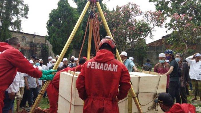 Petugas Suku Dinas (Sudin) Penanggulangan Kebakaran dan Penyelamatan (PKP) Jakarta Timur membantu proses pemakaman warga Klender, Duren Sawit, bernama Abdul Fahmi (25), Selasa (13/7/2021).