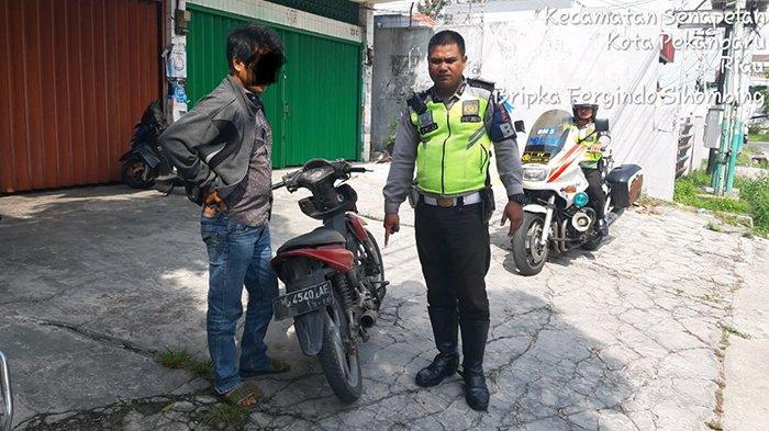 Anggota Satlantas Polresta Pekanbaru saat mengamankan sepeda motor yang menggunakan knalpot racing, Rabu (22/5/2019)/Istimewa